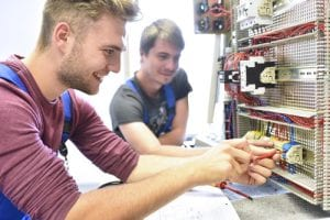 Two electrician students working at electrical panel
